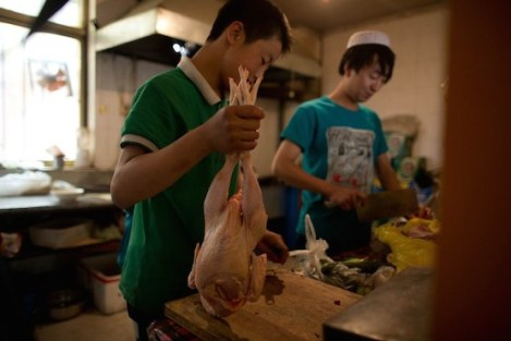 "A photo taken on May 14, 2013 shows two cooks preparing chicken at a halal restaurant in Jiayuguan, China's northwestern Gansu province. Cuisine in Gansu is based on the staple crops grown in the region, wheat, barley, millet, beans, sweet potatoes and is known for the Muslim restaurants known as ""qingzhen restaurants"" which feature typical Chinese dishes without any pork products. AFP PHOTO / Ed Jones / AFP / Ed Jones"